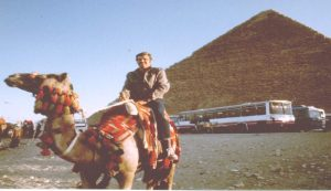 photo of camel rider and the giant pyramid